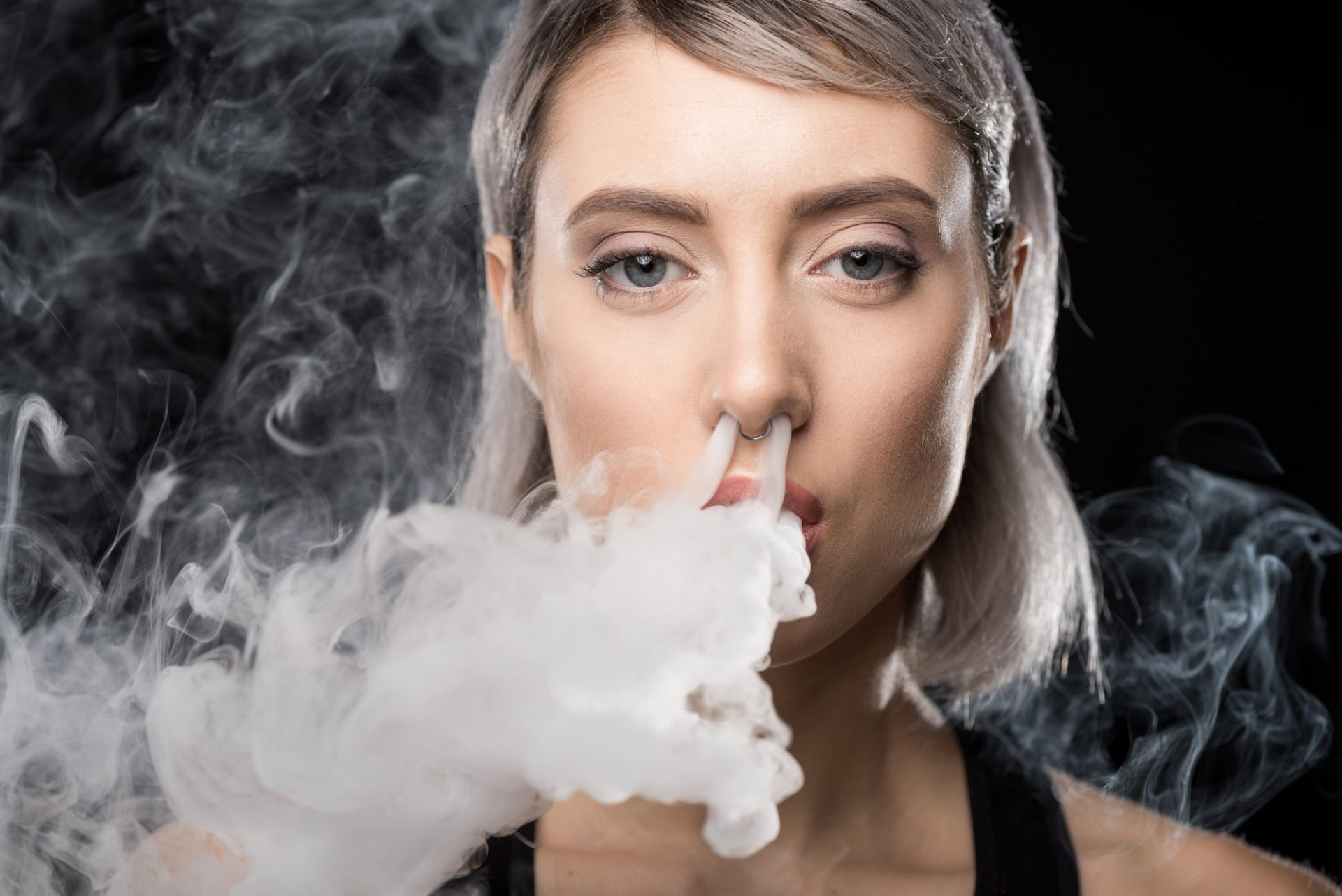Young woman vaping and blowing smoke of electronic cigarette from nose